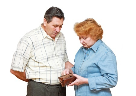 A senior couple looking at an empty wallet