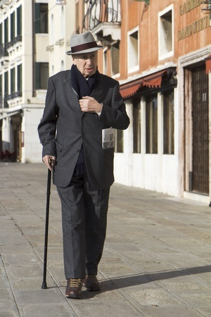elderly gentleman walking in Italy with a cane