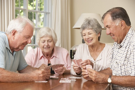 42164351 - group of senior couples enjoying game of cards at home
