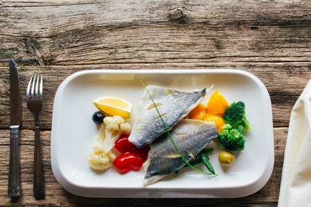 54302172 - dorado fillet with little stewed vegetables on a white square plate. boiled fish fillets with a garnish of vegetables. lenten food. lenten food served on a wooden background