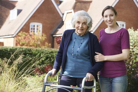 54532356 - daughter helping senior mother to use walking frame