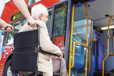 31018343 - senior couple boarding bus using wheelchair access ramp